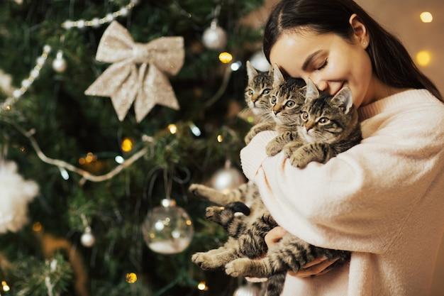 Menina feliz segurando três gatinhos doces perto da árvore de natal