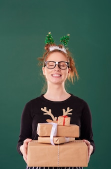 Menina feliz segurando uma pilha de presente de natal