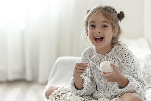 Menina feliz sentada no sofá e aprendendo a tricotar, o conceito de lazer em casa.