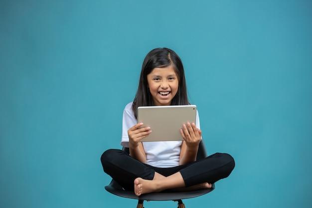 Menina feliz, sentado em uma cadeira assistindo tablet