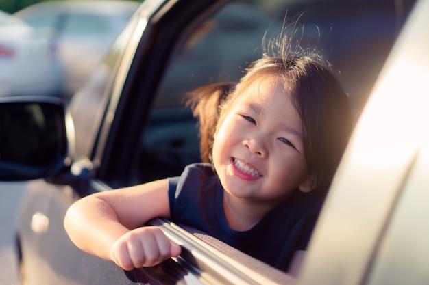 Menina feliz sentado no carro e sorrir