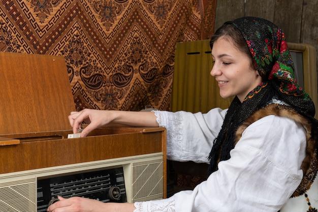 Menina feliz smilimg em roupas nacionais ucranianas, ouvindo música no rádio retrô