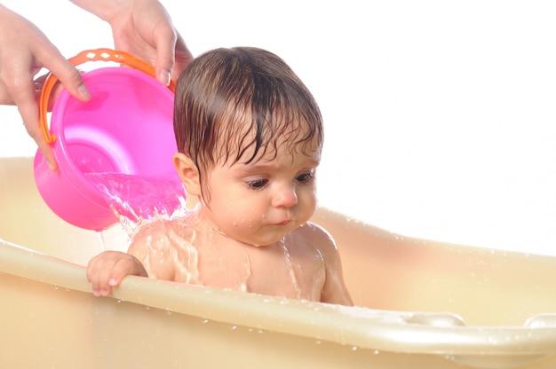 Menina feliz sob salpicos de água no banho