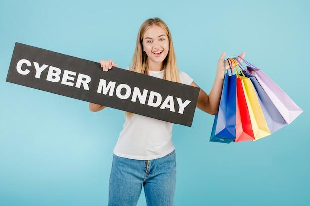 Menina feliz sorridente com sinal de cyber segunda-feira e sacolas coloridas isoladas sobre azul