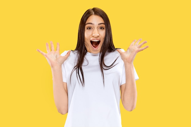 Menina feliz, sorridente e surpresa. belo retrato feminino de meio comprimento isolado na parede amarela. jovem mulher sorridente. espaço negativo. expressão facial, conceito de emoções humanas.