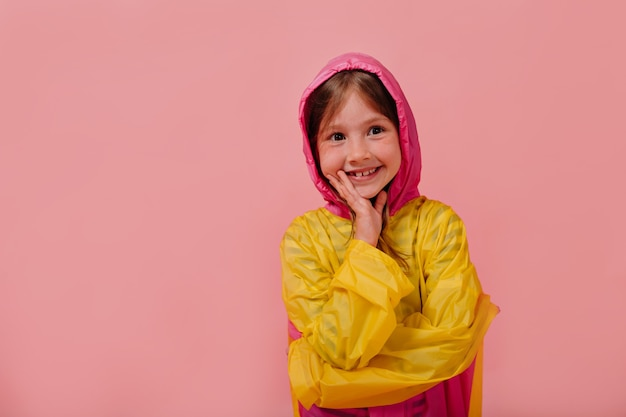 Menina feliz sorridente usando capa de chuva brilhante, sorrindo e segurando a mão perto do rosto