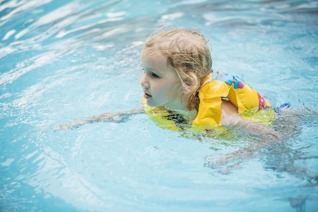 Menina feliz sorrindo e nadando na piscina ao ar livre linda e feliz