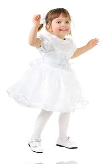 Menina feliz sorrindo e posando de vestido branco e sapatos