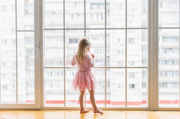 Menina feliz sorrindo em pé na frente da janela