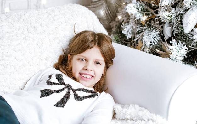 Menina feliz sorrindo em um sofá no interior de natal ao lado da árvore de natal