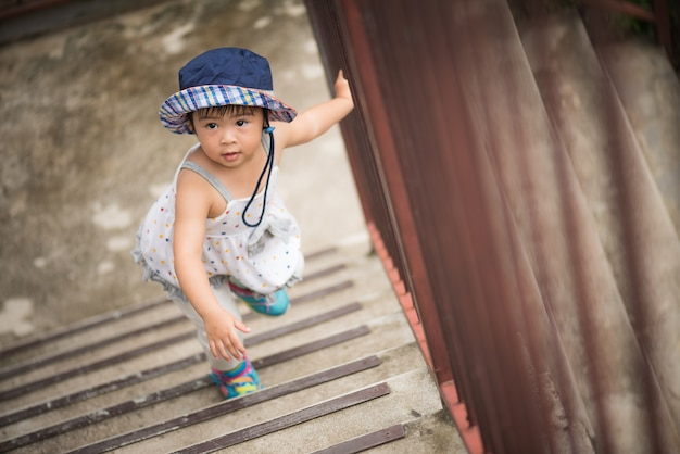 Menina feliz subindo as escadas. kid primeiro conceito passo.
