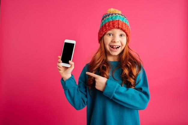 Menina feliz surpresa, mostrando o smartphone com tela em branco e sorrindo isolado