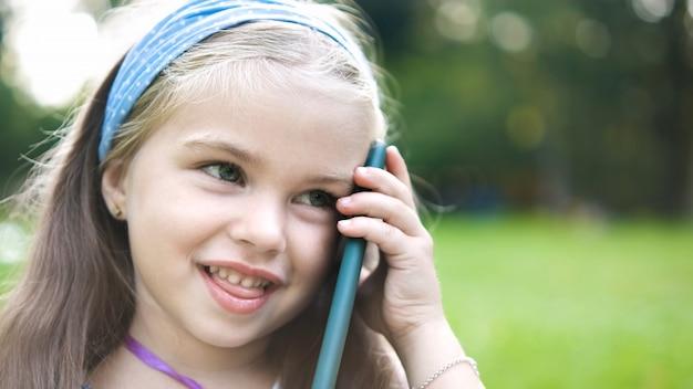 Menina feliz tendo uma conversa falando no celular no parque de verão.