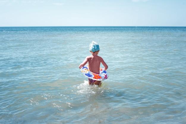 Menina feliz toma banho na água azul em um círculo inflável