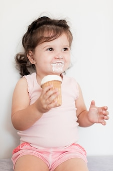 Menina feliz, tomando um sorvete