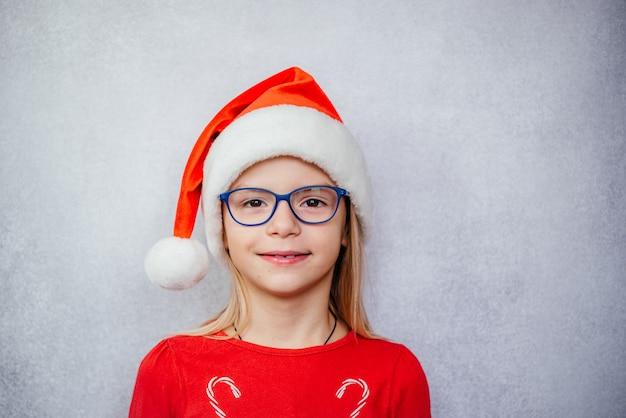 Menina feliz usando óculos e chapéu de papai noel durante as férias de natal e ano novo