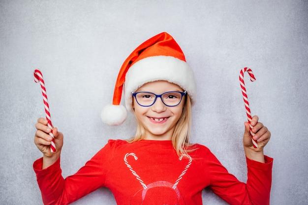 Menina feliz usando óculos e chapéu de papai noel, segurando bastões de doces durante as férias de natal e ano novo, teste de visão de crianças