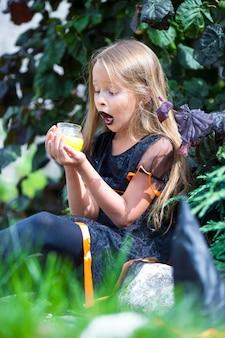 Menina feliz vestindo fantasia de bruxa no dia das bruxas ao ar livre. doçura ou travessura.