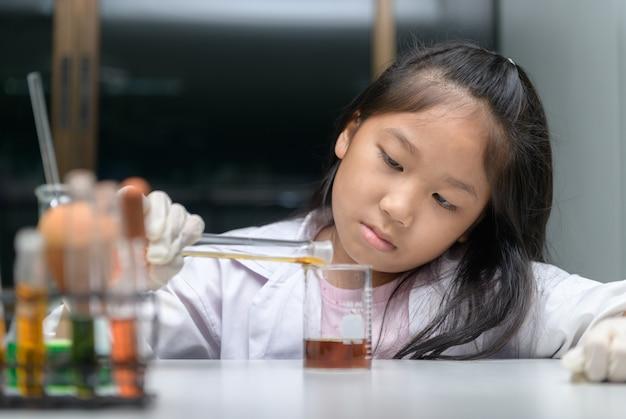 Menina feliz vestindo jaleco fazendo experimento