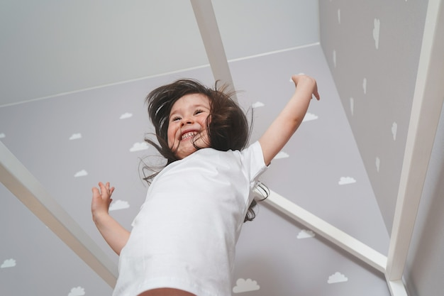 Menina feliz vestindo pijama branco pulando na cama no quarto branco. linda garota se divertindo enquanto pular e brincar