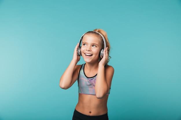 Menina feliz vestindo roupas esportivas e ouvindo música com fones de ouvido isolados na parede azul