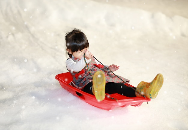 Menina feliz vestindo um casaco vermelho-cinza se diverte na neve