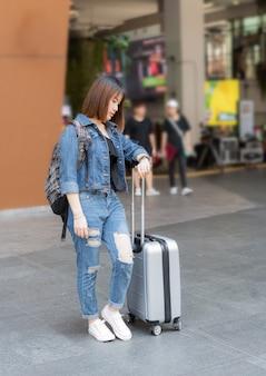 Menina feliz viajante asiático com bagagem procurando um relógio para reunião