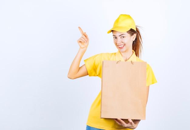 Menina feminina em uniforme amarelo segurando uma sacola de papelão e apontando para algum lugar.