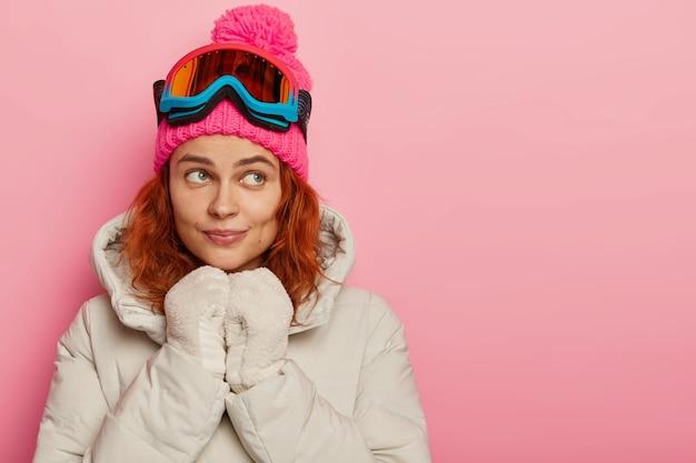 Menina feminina pensativa com cabelo ondulado ruivo usa chapéu, casaco e luvas quentes, usa óculos de snowboard de proteção, poses internas contra um fundo rosa.