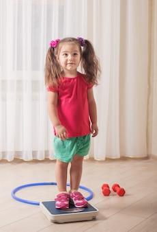 Menina fica em balanças de chão no piso de madeira na sala de estar