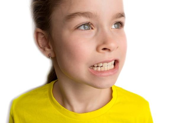 Menina fica em um fundo branco com um lindo sorriso, dentes tortos de crianças, odontopediatria. close-up de dentes tortos. a correção da má oclusão é necessária. foto de alta qualidade