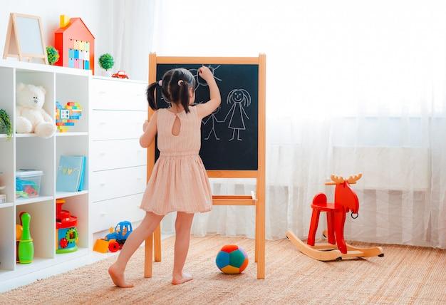 Menina fica no quarto das crianças com um quadro negro e desenha uma família com giz