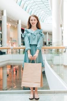 Menina, ficar, com, bolsas para compras, em, centro comercial