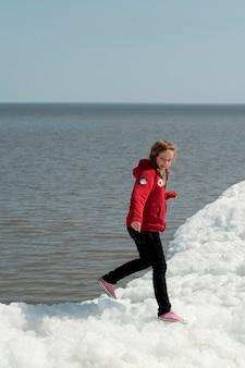 Menina, ficar, ligado, um, pilha neve, em, winnipeg, praia, manitoba, canadá