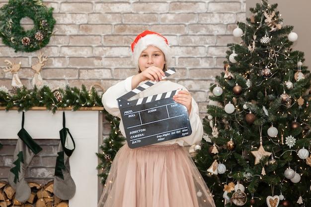 Menina filmando filme de natal na festiva sala de estar