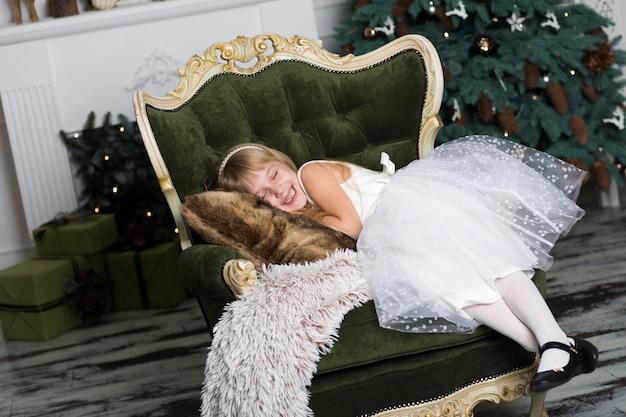 Menina fingindo estar dormindo em uma poltrona perto de uma árvore de natal para conhecer o papai noel quando ele traz presentes