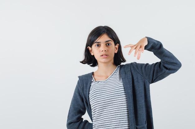 Menina fingindo segurar ou mostrar algo em uma camiseta, jaqueta e parecendo confusa
