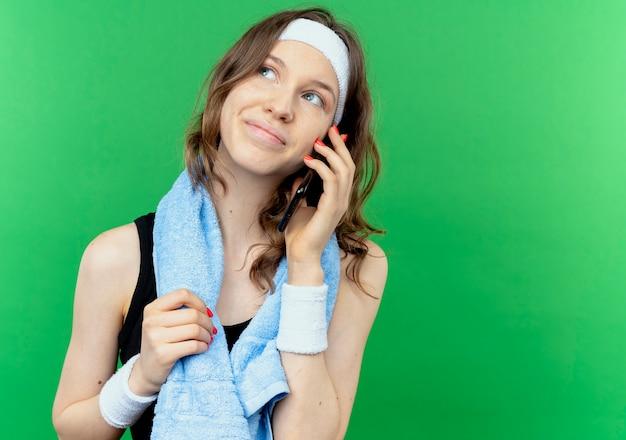 Menina fitness jovem em sportswear preto com fita para a cabeça e toalha ao redor do pescoço, sorrindo enquanto fala no telefone celular sobre o verde