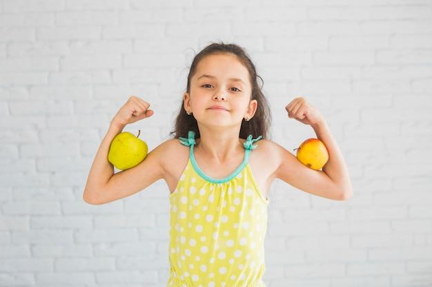 Menina, flexionar, dela, mãos, segurando, maçã, dela, bíceps