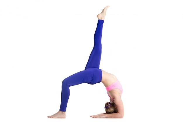 Menina flexível em uma ioga do pose difícil