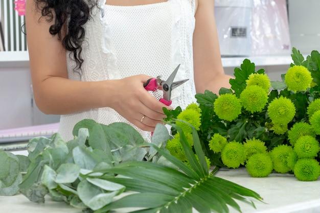 Menina florista ameixas crisântemos verdes. criando um buquê de flores frescas.