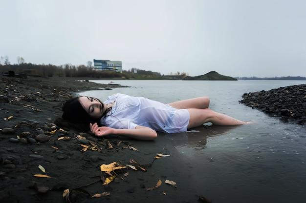 Menina flutuando deitada na rocha de um rio escuro