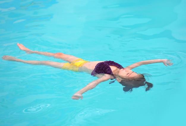 Menina flutuando na superfície da água da piscina