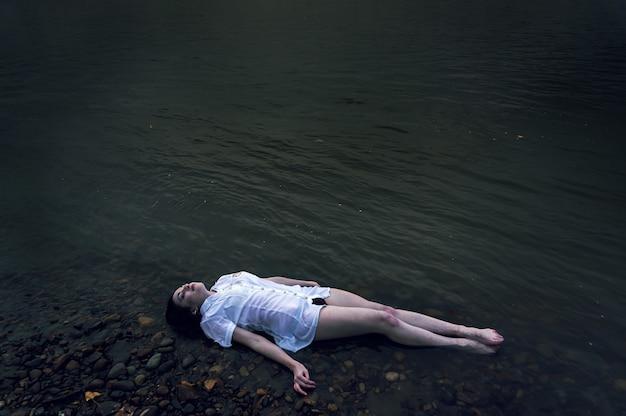 Menina flutuante deitada sobre a rocha do rio escuro. ofélia conceitual