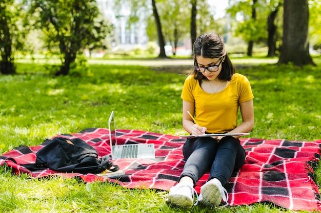 Menina focada estudando no parque Foto gratuita
