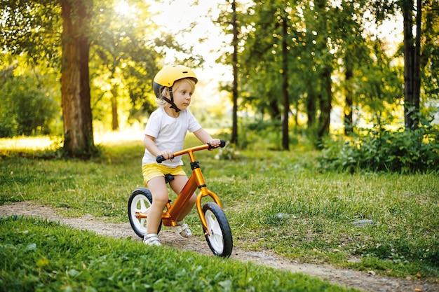 Menina fofa adorável criança caucasiana se divertindo equitação exercício equilíbrio correr bicicleta empurrar scooter ...