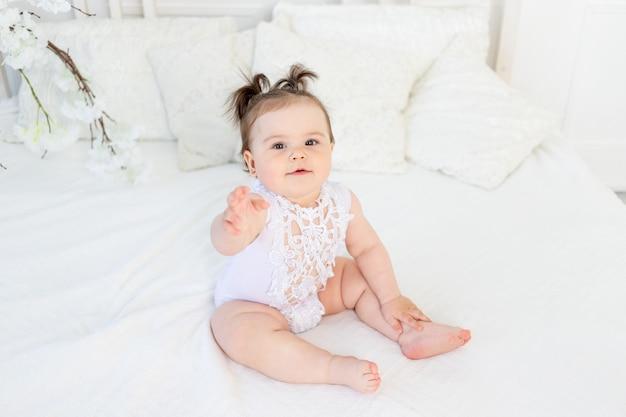 Menina fofa com macacão branco na cama em casa no quarto bem iluminado