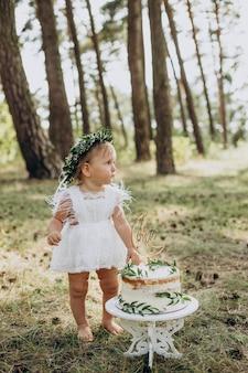 Menina fofa com seu primeiro bolo de aniversário