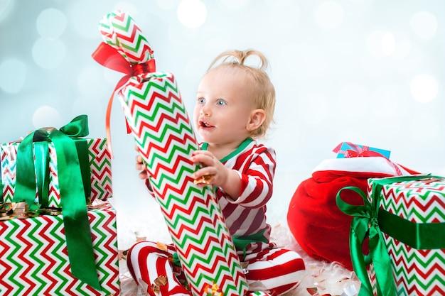 Menina fofa de 1 ano perto de chapéu de papai noel posando no natal