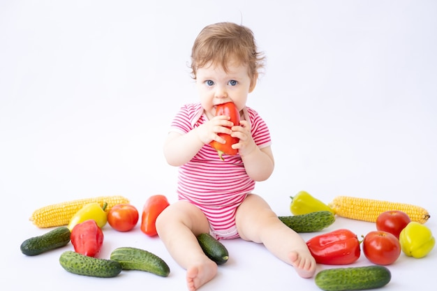 Menina fofa e saudável em um macacão rosa sentada com vegetais em um fundo branco isolado
